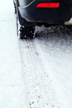 road conditions: Traces of snow tires in the snow on the roadway of a street