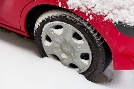 road conditions: Winter tires of a car in the snow. Driving in the winter.