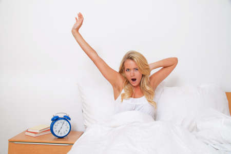 buonanotte: Giovane donna graziosa alzarsi e svegliarsi. Buon umore del mattino a letto