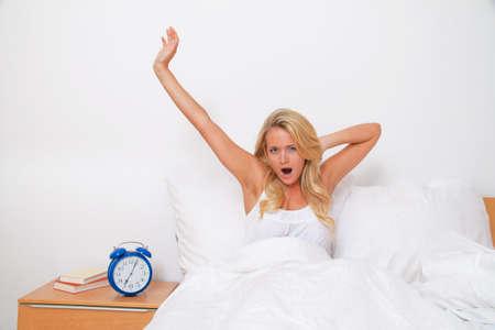 akkoord: Jonge mooie vrouw opstaan en wakker. Goed humeur in de ochtend in bed