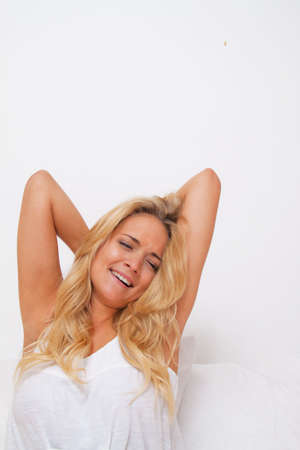 good mood: Young pretty woman getting up and waking up. Good mood in the morning in bed Stock Photo