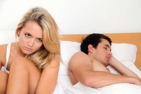 rejections: A young couple in bed having problems and crisis. Divorce and separation.