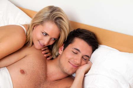 sexo cama: Pareja tiene diversi�n en la cama. La risa, la alegr�a y el erotismo en el dormitorio