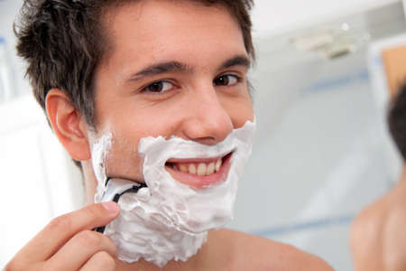 shaving cream: Young man shaving with razor and shaving cream in bathroom Stock Photo