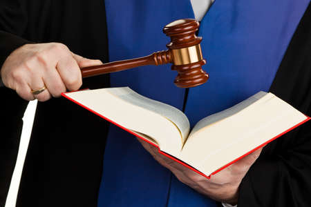 judiciary: A judge with a law book in court. With Justice figure in the hand. Stock Photo