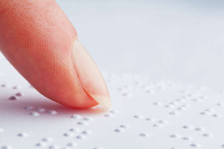 accessibilit�: Dita e Braille. Le persone non vedenti di leggere un libro in Braille.