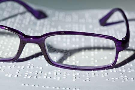braille: Un par de gafas y un libro en Braille. Leer con discapacidad.