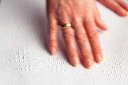 Vingers en braille. Blinde mensen lezen een boek in braille.