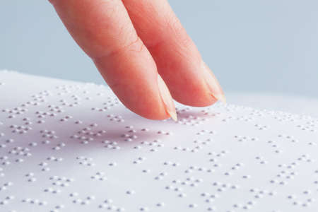 braille: Fingers and Braille. Blind people read a book in Braille.