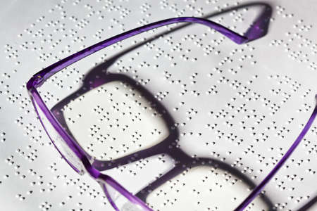 A pair of glasses and a book in Braille. Read with disabilities. Stock Photo - 8840208