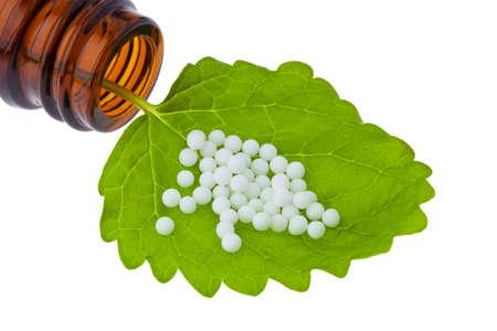 Homeopatía. Glóbulos como medicina alternativa. Acostado en una hoja.