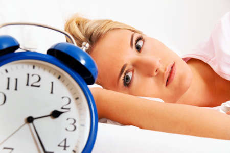 Orologio con il sonno di notte. Donna non riesce a dormire. Archivio Fotografico