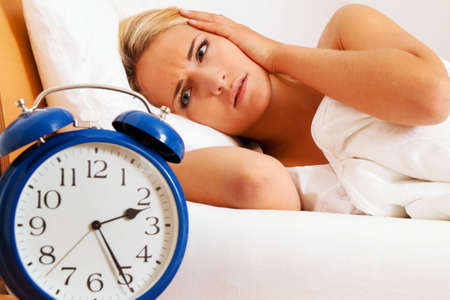 resting heart rate: Clock with sleep at night. Woman can not sleep. Stock Photo