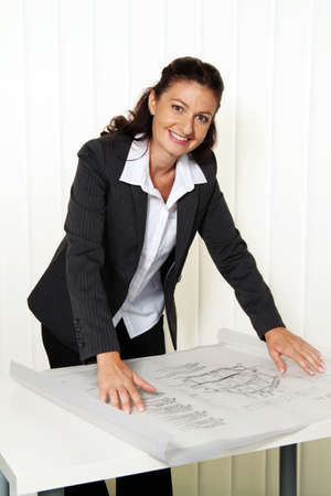 entrepreneurial: Architect with blueprint in the office. Plans of a house are processed