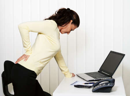 arthritis pain: Woman with back pain of the intervertebral disc in office