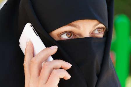mujeres musulmanas: Symbolfoto Islam. Las mujeres musulmanas con velos y burkas est� al tel�fono con tel�fono celular. Foto de archivo