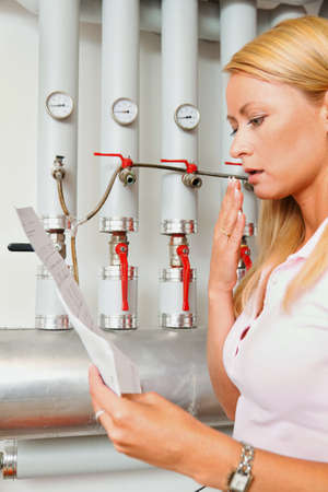 A young woman with a billing of heating costs for heating. In the boiler room. Stock Photo - 8910803