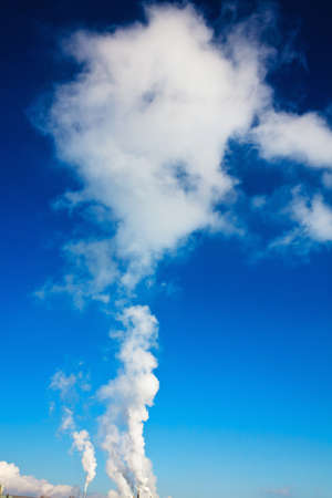particulate: Industrial waste gases from a chimney. Smog cloud of smoke against a blue sky. Stock Photo