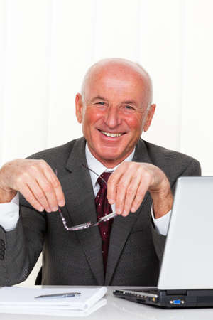 entrepreneurial: A successful older businessman sits in his office with a laptop.
