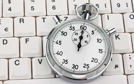 expense: A stopwatch is on a computer keyboard. Cost of labor.