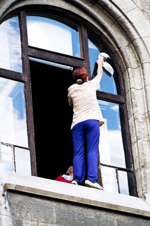 clean home: A woman washing windows. Danger when cleaning the house.