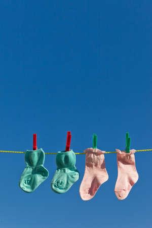 ifestyle: Baby socks on clothesline to dry. Blue sky.