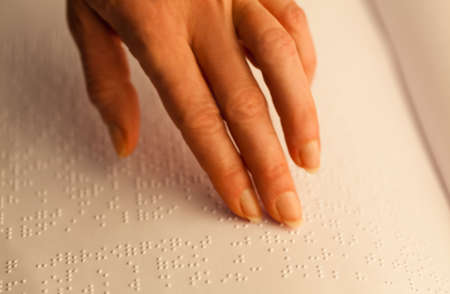 Fingers and Braille. Blind people read a book in Braille. photo