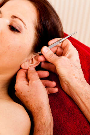 Relaxation, peace and well-being through massage. Ear point massage photo