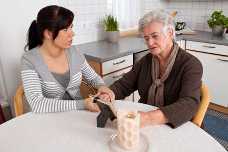 the dying: A young woman comforting a widow after death. Bereavement support. Stock Photo