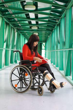 orthopaedics: Una mujer joven con pierna emitidos sentado en una silla de ruedas Foto de archivo