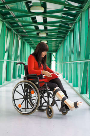 household accident: Young woman with leg cast sitting in a wheelchair Stock Photo