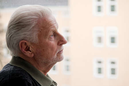 withdrawn: a senior is lonely, depressed, sad case of window Stock Photo