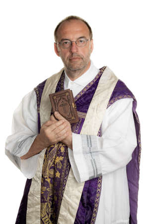 theologian: a Catholic priest with a bible in worship Stock Photo