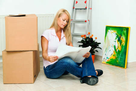 makelaardij: Vrouw met kartonnen dozen over verhuizen naar het nieuwe appartement.