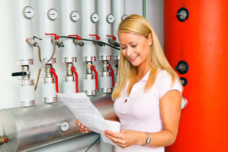 A young woman in the boiler room for heating. Save energy photo