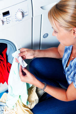 washing clothes: A young housewife with washing machine and clothes. Washing day. Stock Photo
