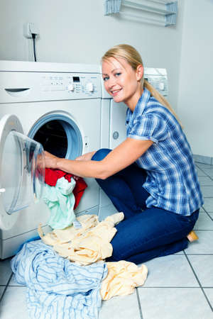 detergents: A young housewife with washing machine and clothes. Washing day. Stock Photo