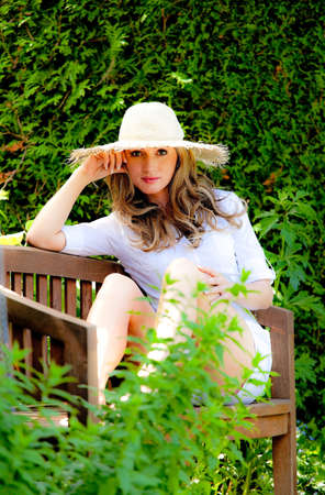 sun hat: Young woman in the garden relaxing. With a sun hat Stock Photo