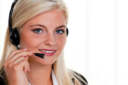 fixed line: Young woman with telephone headset in a call center Stock Photo