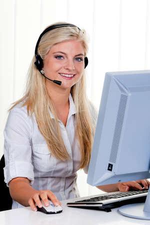 Jonge vrouw met hoofdtelefoon op computer hotline. Stockfoto