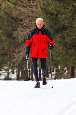 Senior at the snow in winter nordic walking photo