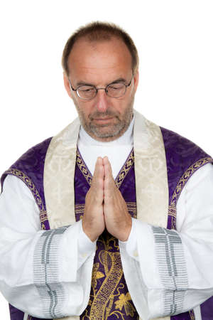 theologians: A Catholic priest in praying against a white background Stock Photo