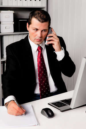 Young businessman in the office with phone from a laptop Stock Photo - 9445461