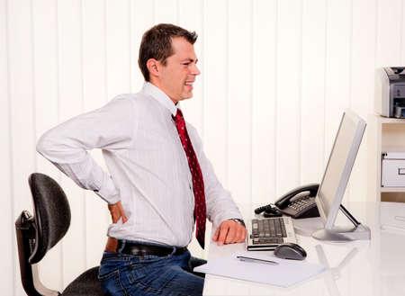 dolor de espalda: Joven hombre de oficina con equipo y dolor de espalda Foto de archivo