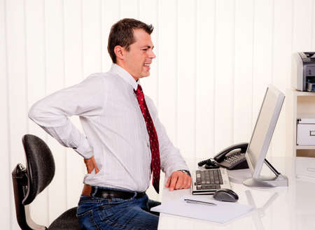 Young man in office with computer and back pain photo
