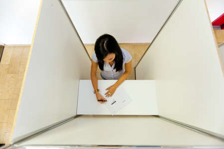 local election: Young woman in a polling booth in the electorate casting their vote