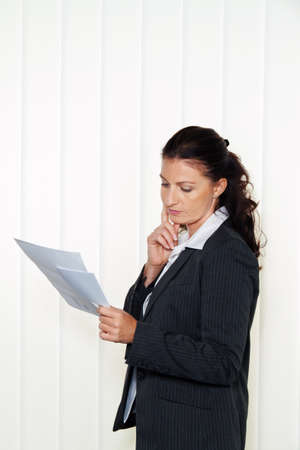 summons: Businesswoman reading a letter in the office. Message from the attorney or tax office.