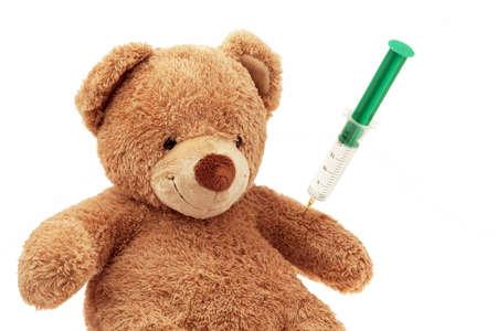Un peluche obtiene una inyección. Vacunas y jeringuillas.