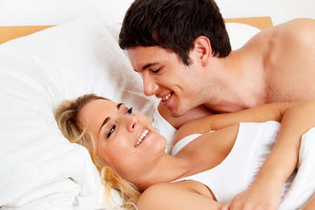 Couple has fun in bed. Laughter, joy and eroticism in the bedroom photo