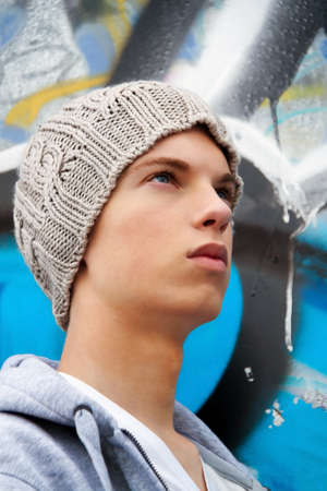 A cool-looking young man in front of graffiti photo